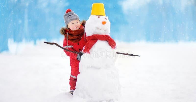 Pysen i röd vinterkläder som har gyckel med snögubben i snöig, parkerar royaltyfria bilder