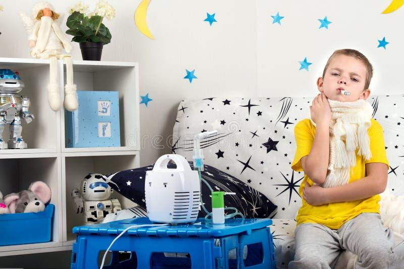 Pysen känner sig för att smärta i halsen, mäter temperaturen Barnet gör inandningnebulizeren arkivfoton