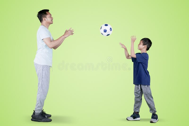 Pysen kastar en fotbollboll till hans fader arkivfoto