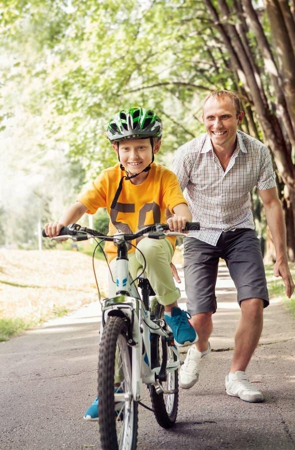Pysen lär att rida cykeln med hans fader royaltyfria bilder