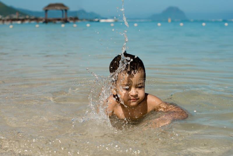 Pysen ligger på stranden av Indiska oceanen och är lek royaltyfria bilder