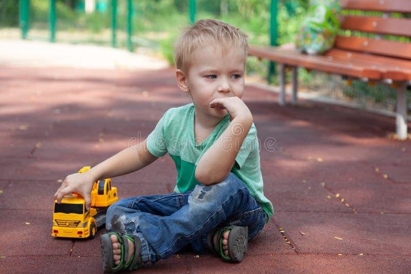 Pysen med blåa ögon sitter på räkningen av barnlekplatsen med en leksak - gul grävskopa Blont hår, fundersam blick, al arkivfoton