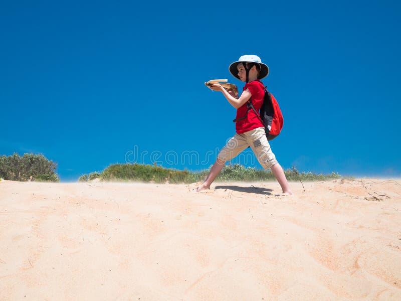 Pysen med en ryggsäck och en armborst i hans händer står på de guld- sanderna, och tagande siktar arkivfoton