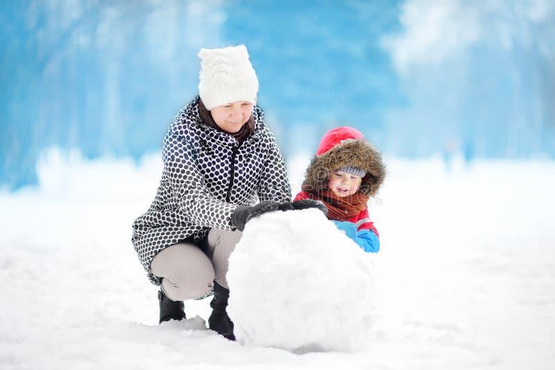 Pysen med hans moder-/babysitter-/farmorbyggnadssnögubbe i snöig parkerar fotografering för bildbyråer