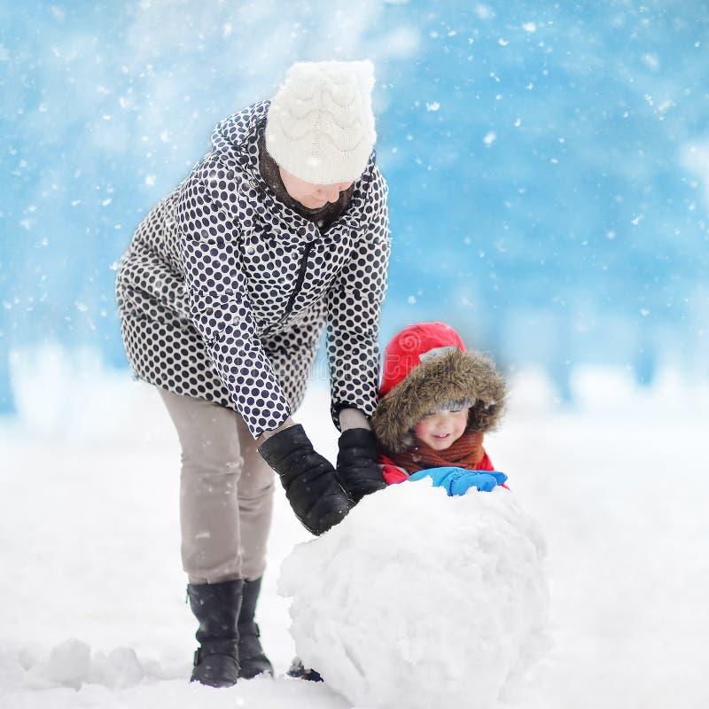 Pysen med hans moder-/babysitter-/farmorbyggnadssnögubbe i snöig parkerar arkivbild