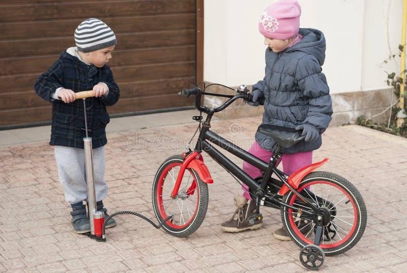 Pysen och flickan reparerar en cykel arkivbilder