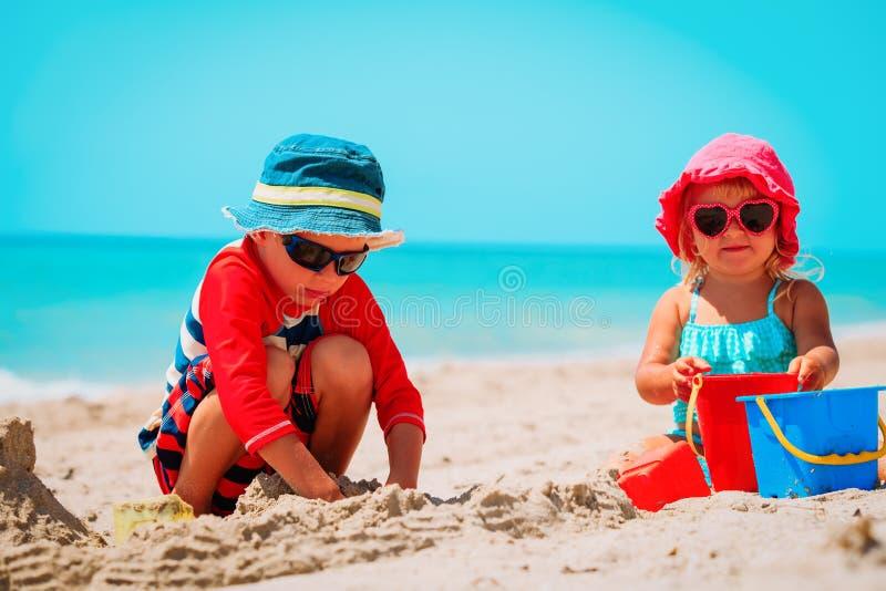 Pysen och flickan spelar med sand på stranden arkivbild