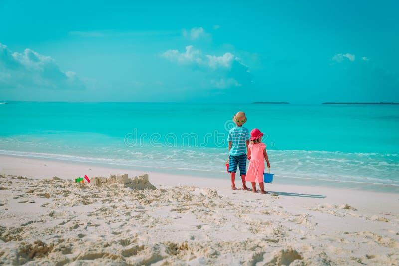 Pysen och flickan spelar med sand p? stranden arkivfoton
