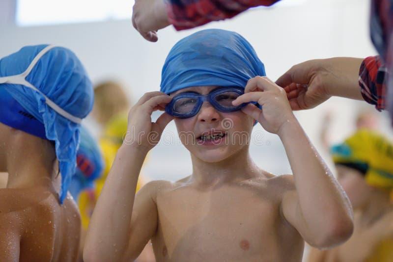Pysen rätar ut hans simma skyddsglasögon i pöl royaltyfri bild