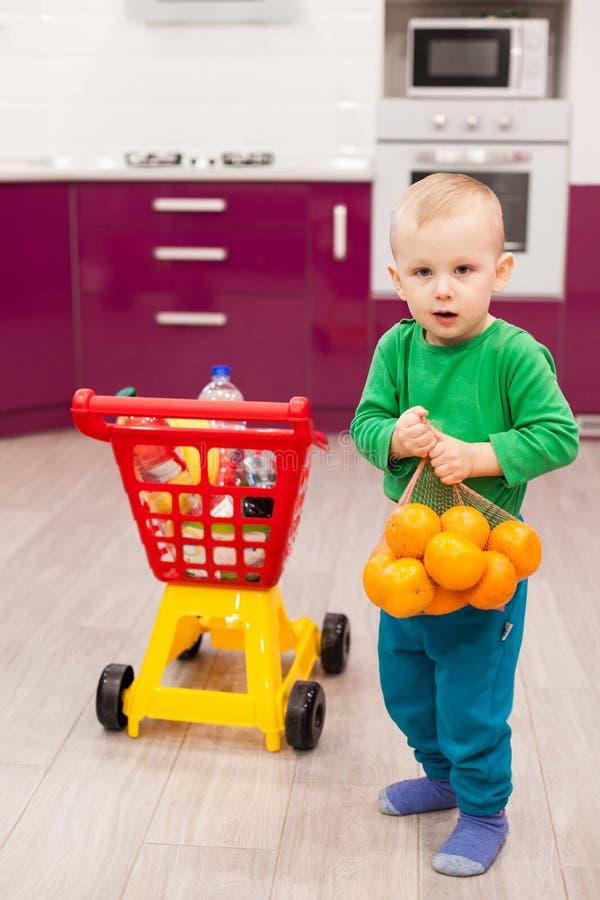 Pysen rymmer ett raster med apelsiner Liten unge i spårvagn för barn för tillfälliga kläder bärande plast- shoppa royaltyfri bild