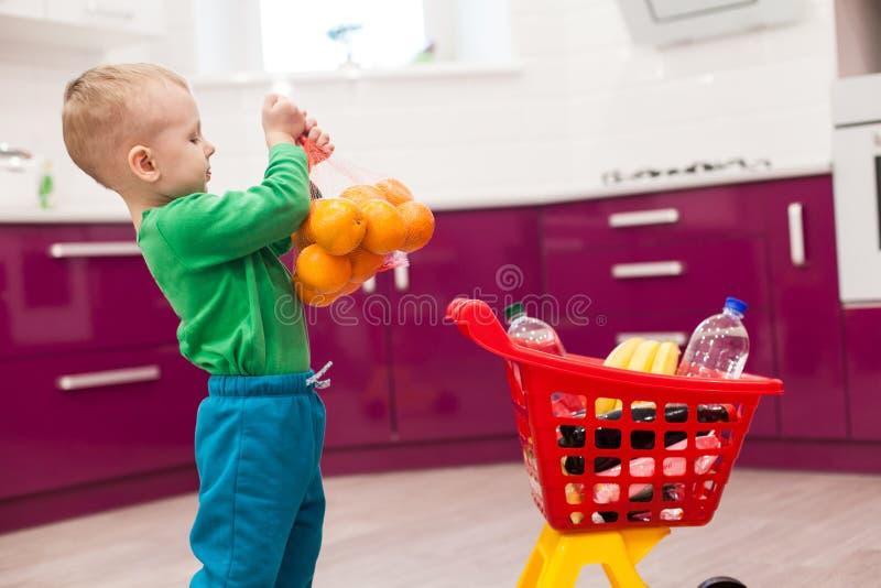 Pysen rymmer ett raster med apelsiner Liten unge i spårvagn för barn för tillfälliga kläder bärande plast- shoppa fotografering för bildbyråer