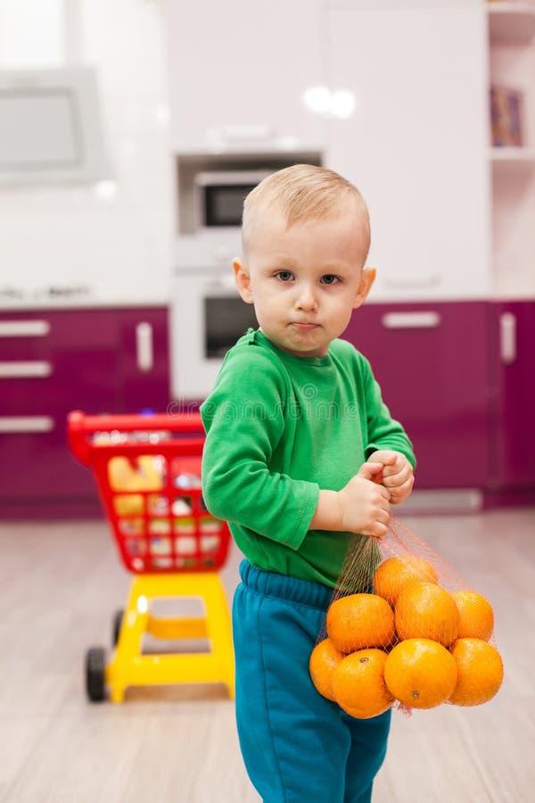 Pysen rymmer ett raster med apelsiner Liten unge i spårvagn för barn för tillfälliga kläder bärande plast- shoppa arkivbild