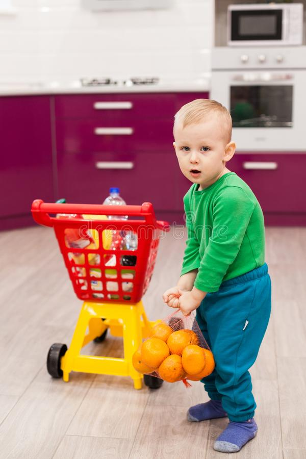 Pysen rymmer ett raster med apelsiner Liten unge i spårvagn för barn för tillfälliga kläder bärande plast- shoppa arkivfoto