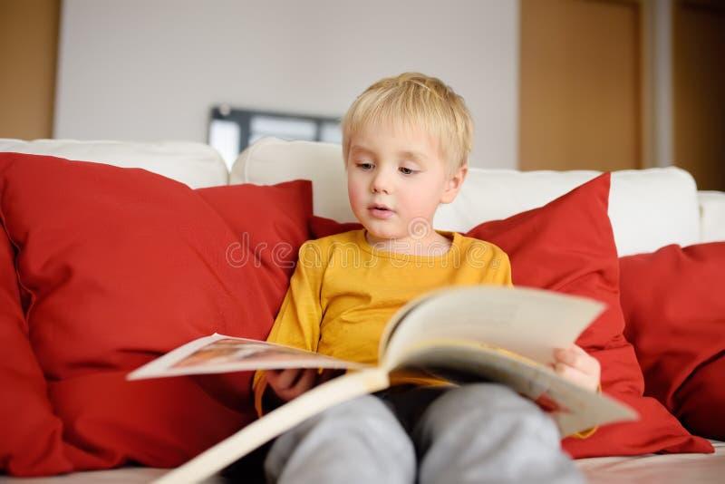 Pysen sitter hemma på soffan och läser en bok lära som läs till royaltyfri fotografi