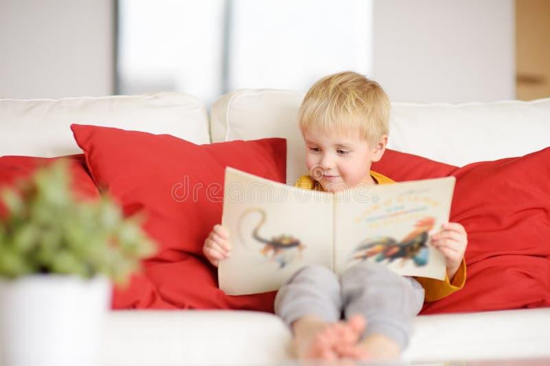 Pysen sitter hemma p? soffan och l?ser en bok l?ra som l?s till arkivbild