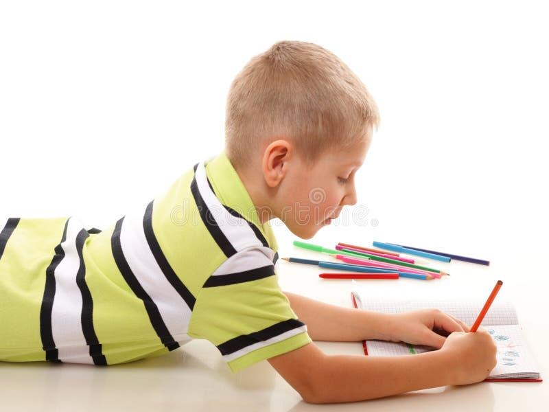 Den unga pojken som attraktioner med färgar, ritar isolerat royaltyfri fotografi