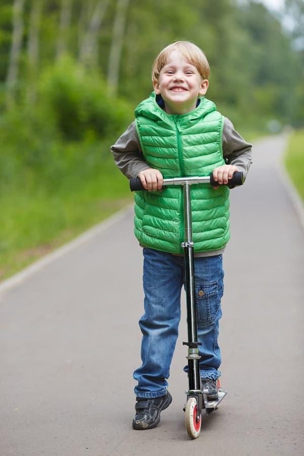 Pysen som ler på en sparkcykel i, parkerar royaltyfria foton