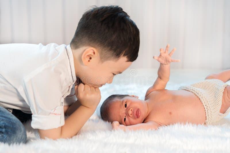 Pysen som ser hans nyfött, behandla som ett barn brodern på säng arkivfoton