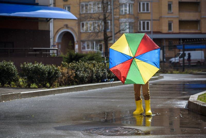 Pysen som spelar i regnig sommar, parkerar Barn med det färgrika regnbågeparaplyet, det vattentäta laget och kängor som hoppar i  arkivfoton
