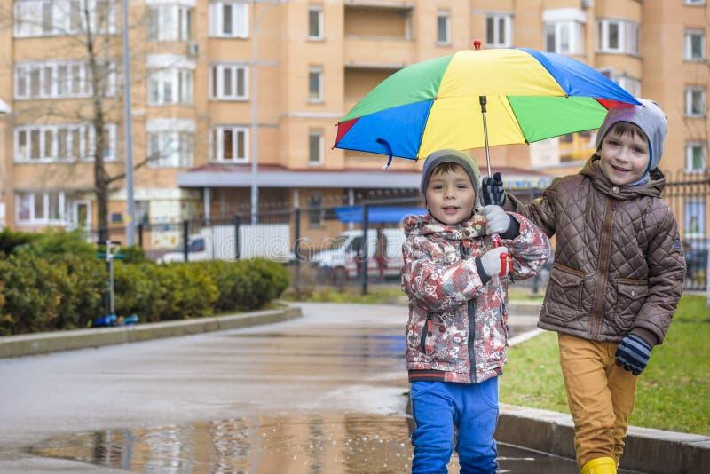 Pysen som spelar i regnig sommar, parkerar Barn med det färgrika regnbågeparaplyet, det vattentäta laget och kängor som hoppar i  royaltyfria bilder