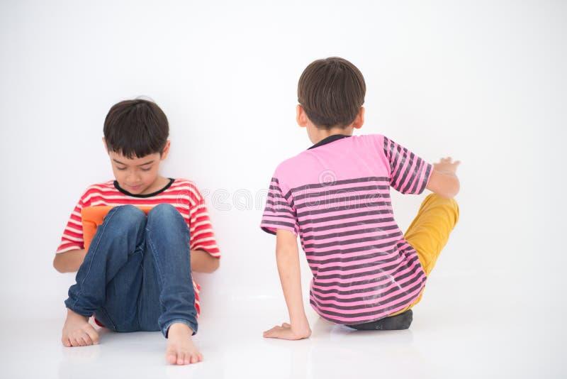 Pysen som spelar minnestavlan, och andra önskar att spela med pojken ingen uppmärksamhet arkivbilder