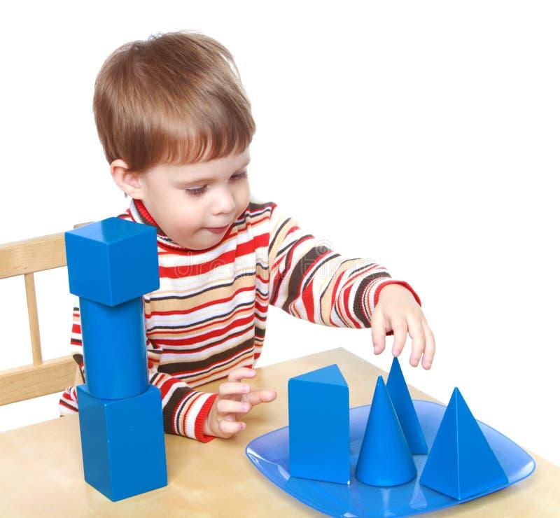 Pysen spelar kuber och kottar som sitter på arkivbild