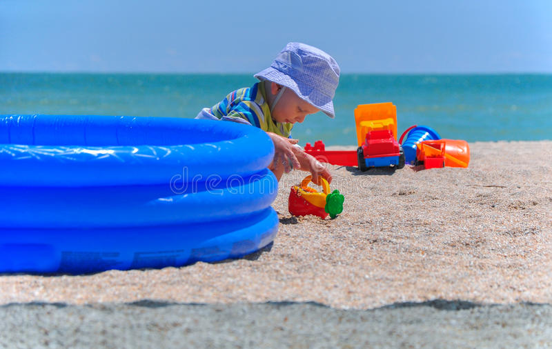 Pysen spelar leksaker i sand på stranden royaltyfri fotografi