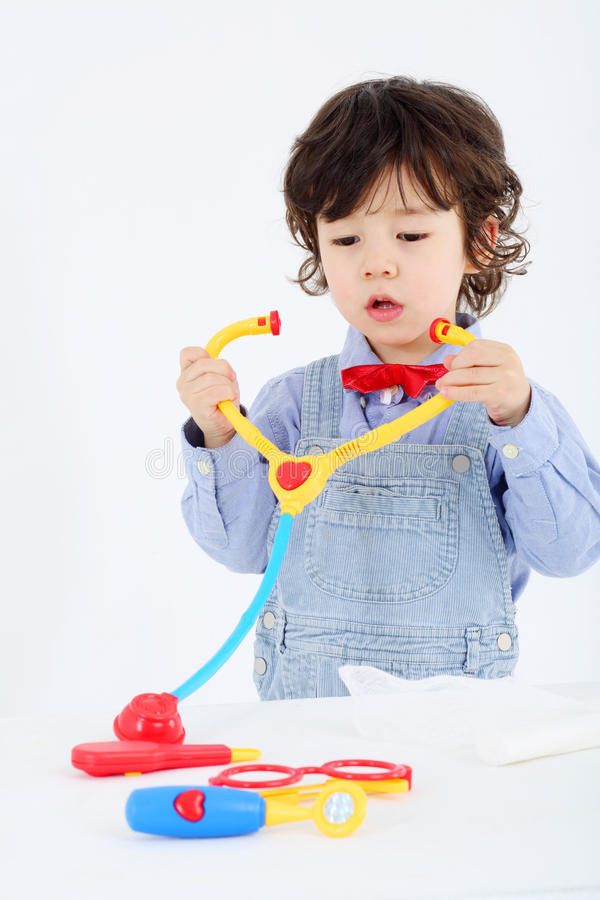 Pysen spelar med leksakphonendoscope och medicinska instrument royaltyfri bild