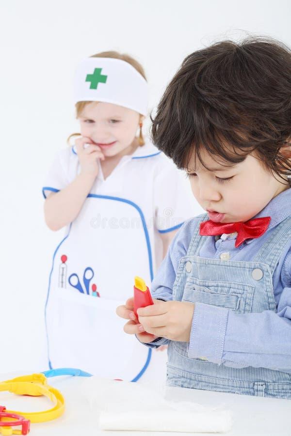 Pysen spelar med medicinska instrument för leksaken, och flickan ser arkivbild