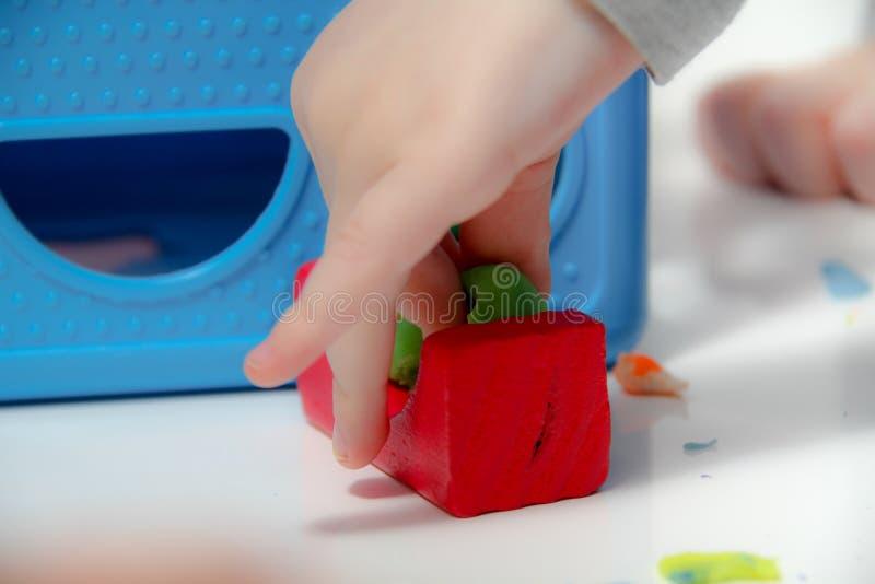 Pysen tre gamla år sitter på tabellen och spelar med plasticine och trä- och plast- leksaker, kuber och tärning royaltyfri bild