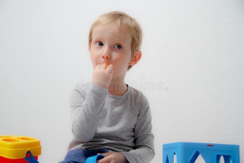 Pysen tre gamla år sitter på tabellen och spelar med plasticine och trä- och plast- leksaker, kuber och tärning arkivfoton