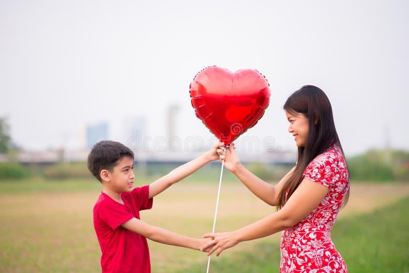 Pyser som ger ballonghjärta till hans moder med förälskelse arkivfoton