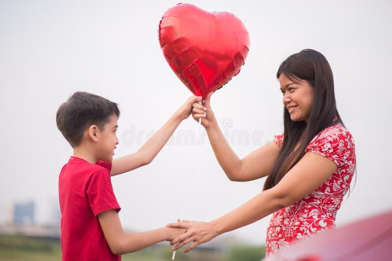 Pyser som ger ballonghjärta till hans moderförälskelse royaltyfria bilder