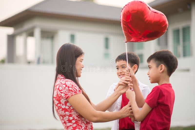 Pyser som ger ballonghjärta till hans moderförälskelse royaltyfri foto