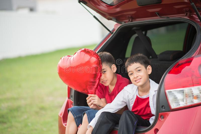 Pyser som ger ballonghjärta till hans moderförälskelse royaltyfri bild