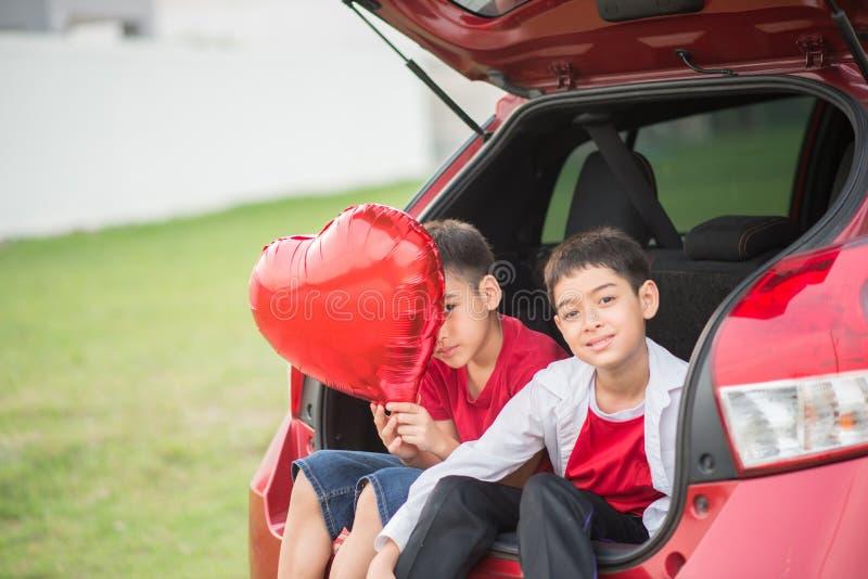Pyser som ger ballonghjärta till hans moderförälskelse royaltyfri fotografi