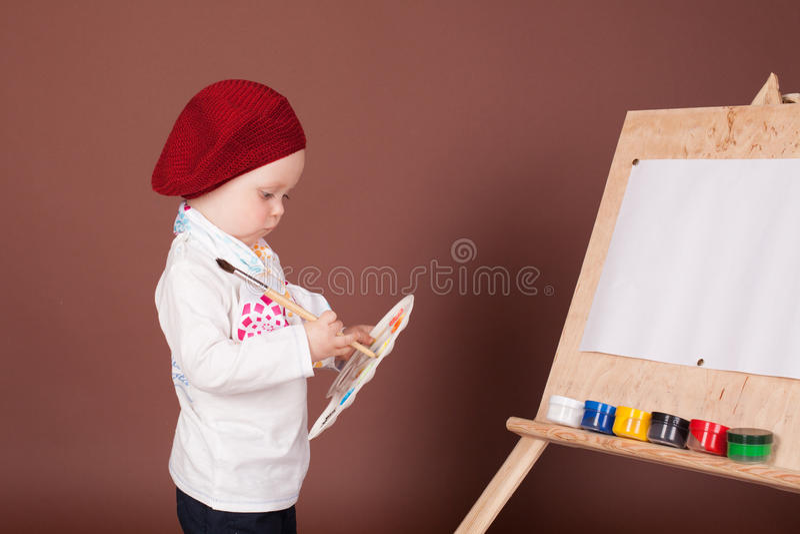 Pyskonstnärborsten och målar målarfärger en bild arkivfoto