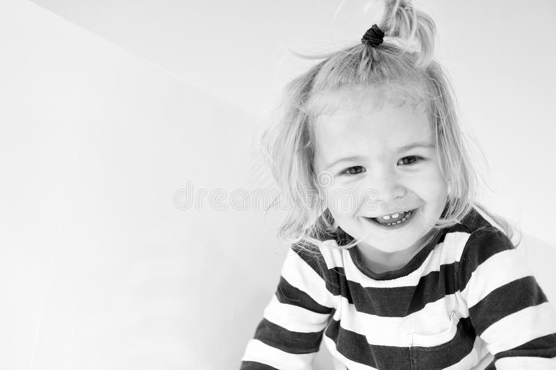 Pysleende i marinkläder Det lyckliga barnet tycker om solig dag Unge som ler med hästsvansen för blont hår Ungar danar och royaltyfria bilder