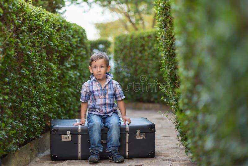 Pyssammanträde på en resväska arkivfoto