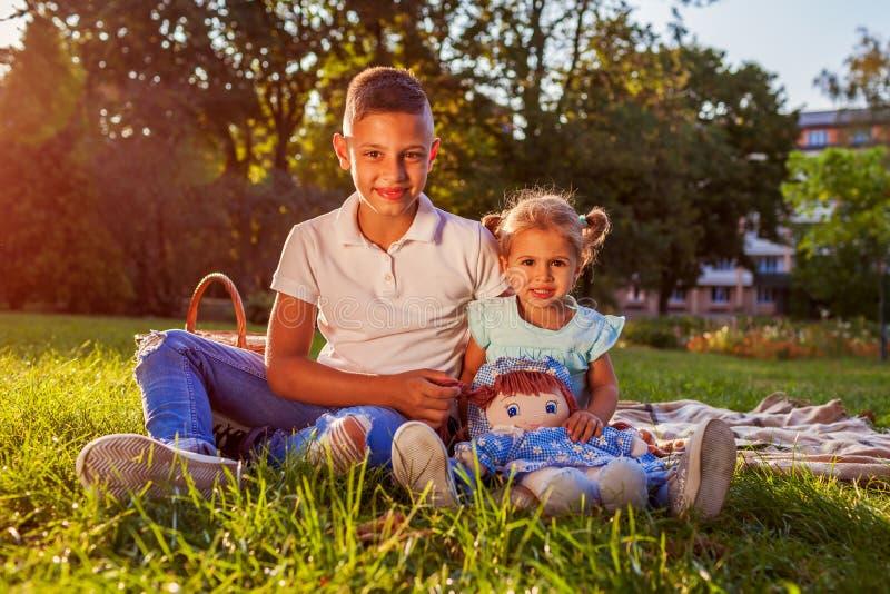 Pyssammanträde på gräs med hans litet barnsyster parkerar in lycklig familj ha picknicken Familjevärderingar royaltyfri foto