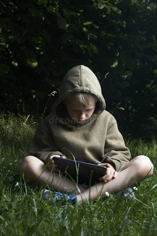 Pyssammanträde på gräs och använda minnestavladatoren royaltyfri foto