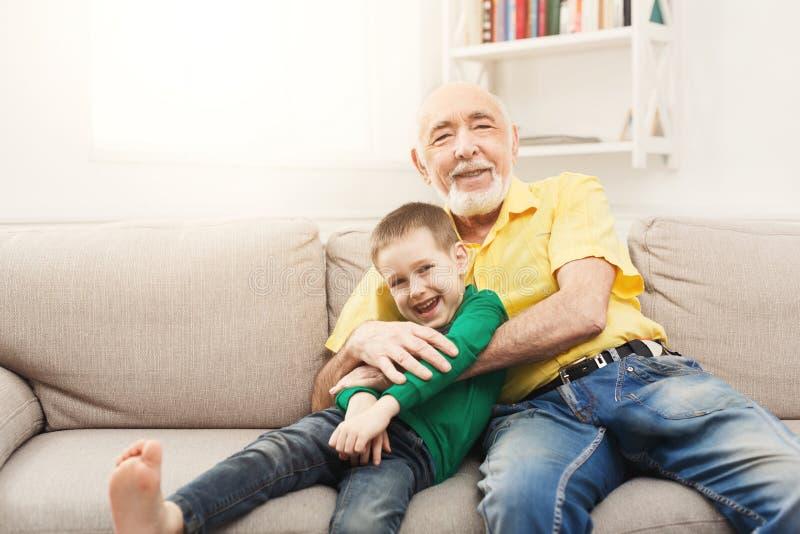 Pyssammanträde på soffan med hans farfar arkivfoton