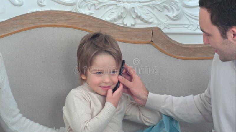 Pyssammanträde på soffan som talar på telefonen, passerade till honom av hans fader arkivfoton