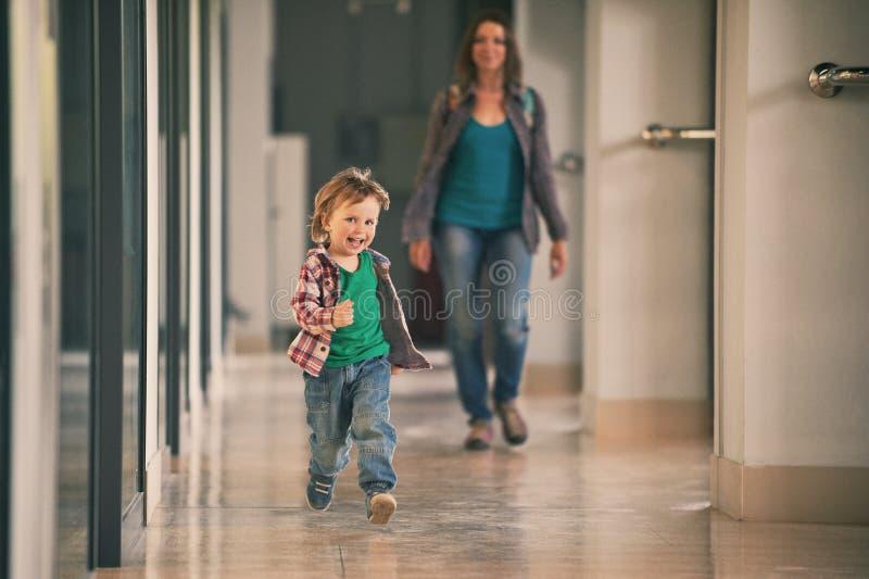 Pysspring i köpcentret med hans mamma på bakgrund arkivfoto