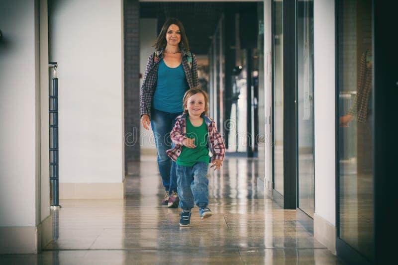 Pysspring i köpcentret med hans mamma på bakgrund arkivbild
