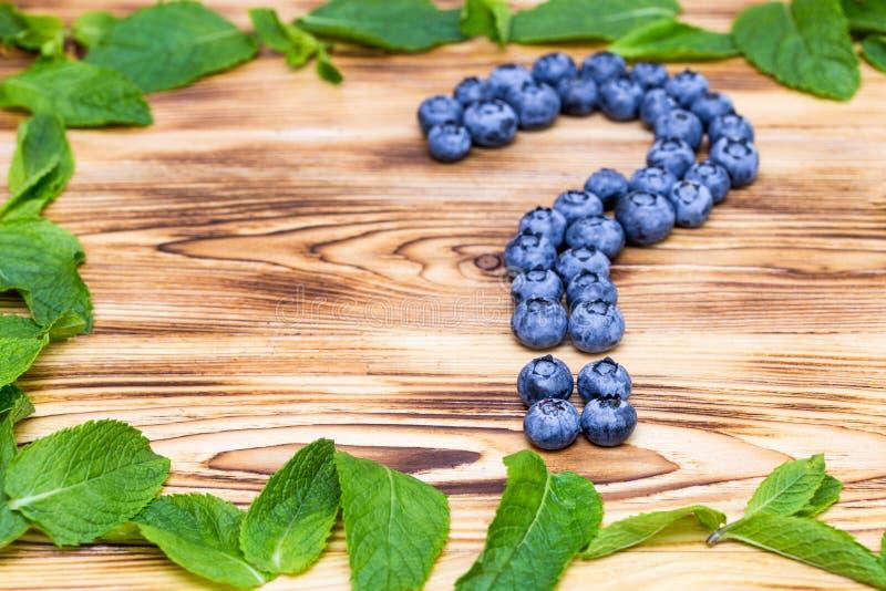 Pytanie znak robić świeże dojrzałe naturalne czarne jagody z jaskrawym - zielona spearmint rama na oczyszczonym drewnianym tle Zd zdjęcie stock