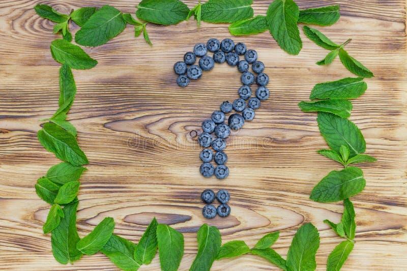 Pytanie znak robić świeże dojrzałe naturalne czarne jagody z jaskrawym - zielona spearmint rama na oczyszczonym drewnianym tle Zd zdjęcia stock