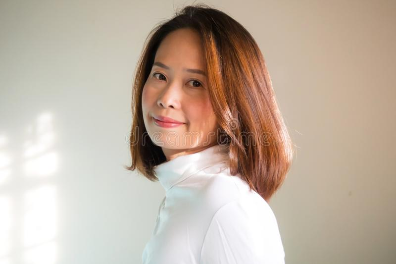 Pyzata azjatykcia kobieta w białej żółw szyi koszulce Portret na whi zdjęcia royalty free