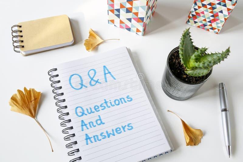 Q&a-frågor och svar som är skriftliga i en anteckningsbok royaltyfria foton