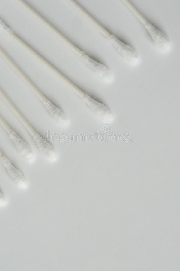 Q tip, or cotton bud swab top view on vertical white background with blank empty space for copy or text; Features best health care. Hygiene practices to clean stock image